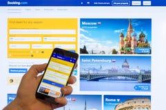旅馆预定互联网售票的主页  在屏幕上的com中国Xiaomi智能手机在计算机上的男性手上 库存图片