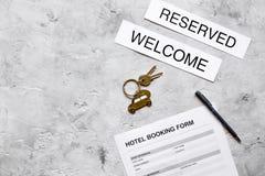 旅馆预订空白和钥匙在石背景顶视图大模型 免版税库存照片