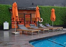 旅馆水池边设定了与大伞,缓冲sundeck椅子&滚动的毛巾在内阁 图库摄影