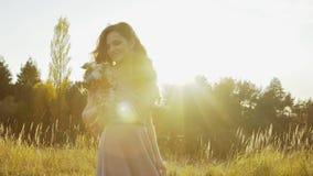 旋转与在干草原中的婚礼花束的可爱的新娘在日落 影视素材