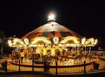 旋转木马在一个游乐园在晚上打开了与明亮的光 免版税库存照片
