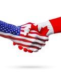 旗子美国和加拿大国家,合作握手 免版税库存照片