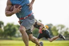 旗标橄榄球球员奔跑 库存照片