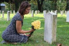 无名战士` s坟墓的妇女与黄色花 库存图片