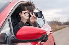 无固定职业的摄影师拍与照相机的照片从汽车 免版税库存照片