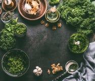 无头甘蓝食谱与新鲜的无头甘蓝叶子和成份的食物背景在黑暗的厨房用桌,顶视图,框架上的pesto的 免版税库存图片