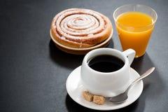 无奶咖啡、甜小圆面包和橙汁在黑背景 库存图片