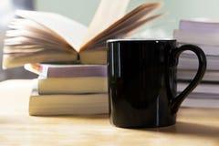 无奶咖啡杯子和书堆 免版税库存照片
