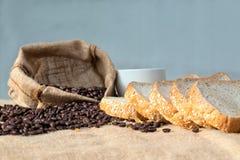 无奶咖啡豆和切的面包与轻的火光 库存图片