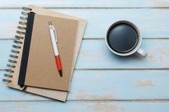 无奶咖啡wth笔记本日志和笔在颜色木地板上 免版税库存图片