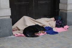无家可归人睡觉粗砺在门道入口 库存照片