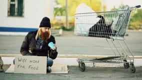 无家可归年轻人计数多少金钱他在手上得到了拿着纸杯和坐在购物车附近在 库存图片