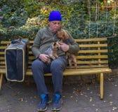 无家可归的人和他的狗坐公园长椅 免版税图库摄影
