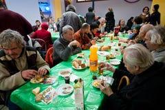 无家可归的人在桌附近坐在可怜的人民的圣诞节慈善晚餐 免版税图库摄影