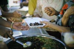 无家可归的人帮助与救济粮食,饥荒安心:给食物的志愿者绝望需要的可怜的人:概念 免版税图库摄影