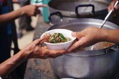 无家可归的人帮助与救济粮食,饥荒安心:给食物的志愿者绝望需要的可怜的人:概念 库存图片