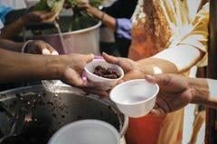 无家可归的人帮助与救济粮食,饥荒安心:给食物的志愿者绝望需要的可怜的人:概念 库存照片