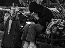 无家可归的人祈祷在他的食物 图库摄影