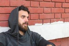 无家可归的人药物和酒精上瘾者单独坐和沮丧在倾斜对红砖大厦墙壁的街道 免版税库存照片
