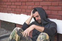 无家可归的人药物和酒精上瘾者单独坐和沮丧在倾斜对红砖大厦墙壁的街道 库存图片
