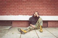 无家可归的人药物和酒精上瘾者单独坐和沮丧在倾斜对红砖大厦墙壁的街道 免版税库存图片