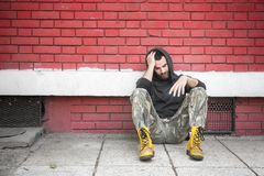 无家可归的人药物和酒精上瘾者单独坐和沮丧在街道 免版税库存照片