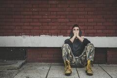 无家可归的人药物和酒精上瘾者单独坐和沮丧在街道 图库摄影