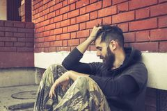 无家可归的人药物和酒精上瘾者单独坐和沮丧在街道 免版税库存图片