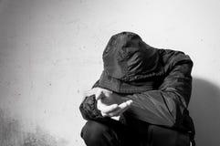 无家可归的叫化子人药物和酒精上瘾者单独坐和沮丧在感觉急切寒冷和l的冬季衣服的街道 免版税库存照片