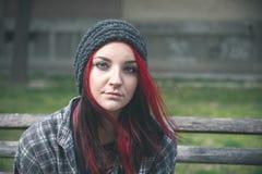 无家可归的女孩,年轻美丽的红色头发女孩单独户外坐充满急切帽子和衬衣的感觉的长木凳 免版税库存图片