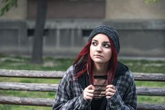 无家可归的女孩,年轻美丽的红色头发女孩单独户外坐充满急切帽子和衬衣的感觉的长木凳 库存照片