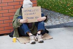 年轻无家可归的男性乞求为帮助 库存图片