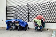 无家可归者个人财产在购物车的在边路 图库摄影