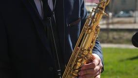 无尾礼服戏剧的萨克斯管吹奏者在金黄萨克斯管 生活表现 演奏萨克斯管爵士音乐的一个人 股票录像