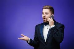 无尾礼服的成功的人和蝶形领结谈话在电话 拿着智能手机,蓝色背景的商人 库存图片