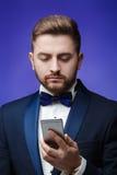 无尾礼服的成功的人和蝶形领结谈话在电话 拿着智能手机,蓝色背景的商人 免版税库存图片