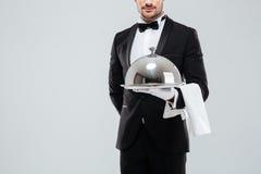 无尾礼服的拿着有盒盖的男管家和手套银色盘子 库存照片