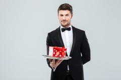 无尾礼服的英俊的男管家有bowtie在盘子的礼物盒的 免版税库存照片