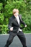 无尾礼服青少年跳跃在绷床 库存图片