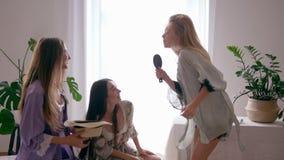 无忧无虑的休息,愉快的女孩唱歌曲入象microphon和舞蹈的发刷与丝绸浴巾的朋友在室 影视素材