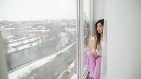 无忧无虑的休闲乏味青少年的女孩坐窗台 库存照片