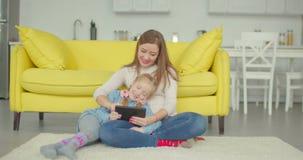 无忧无虑的在网上使用与平板电脑的妈妈和女孩 股票视频