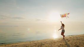 无忧无虑的女孩沿海滩跑,使用与风筝 概念-无忧无虑和愉快的童年 股票视频