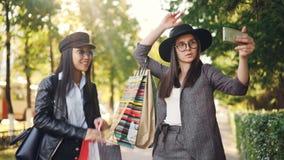 无忧无虑的女孩采取selfie使用摆在与在穿时髦的衣裳的街道的购物袋的智能手机 影视素材