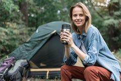 无忧无虑的女孩饮用的饮料在森林里 图库摄影