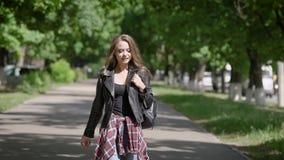 无忧无虑的妇女在一个公园单独走在夏天晴天,漫步在路在绿色树之间,微笑 股票视频