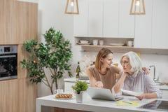 无忧无虑的妇女显示妈妈计算机怎么运转 免版税库存图片