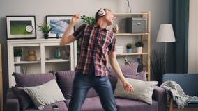 无忧无虑的学生是跳舞和唱听到音乐通过在家放松的耳机享有单独生活 股票视频