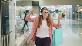 无忧无虑的少女学生在购物中心享用听到音乐通过耳机,跳舞并且唱歌 影视素材