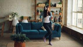 无忧无虑的年轻女人通过耳机在家跳舞听到音乐和移动举胳膊户内在现代 股票录像